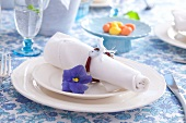 Easter place setting with willow-twig napkin ring and blue pansy