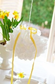 White pompom hanging over set Easter table