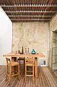 Bar table and matching wooden stools on wooden terrace below steel and wood balcony