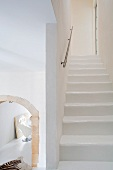 Staircase with modern handrail as reductionist, white spatial sculpture next to historical, stone arched doorway leading to dining area
