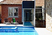 Renovated house with brick, glass and stone facade; garden pool with connection to interior pool