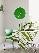 Style mix while dining - modern green chair and white shell chair at a round table with a striped tablecloth in front of a green wall clock in the corner of the room