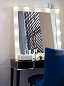 Lighted mirror on a dressing table with beauty products and a blue leather chair