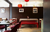 Interior of an Asian restaurant - assorted seating areas some with place settings in front of a dark wooden wall and red lanterns hanging from the ceiling