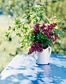 Enamel jug of lilac on wooden table