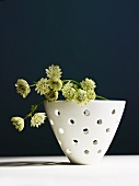 Dried flowers in perforated ceramic bowl