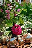 Altes chinesisches Teeporzellan zwischen üppig blühenden Pflanzen
