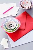 Muffinförmchen als Deko-Blüte auf Briefumschlag