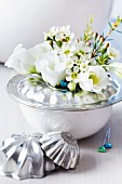 Base of bundt tin on bowl used as vase for waxflowers & lisianthus