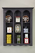Various tea caddies in wall-mounted shelving unit of grey-stained wood