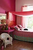 Romantic, girl's bedroom in shades of pink with white wicker chair, pink bedside table, bed with patterned bedspread and canopy
