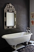 Vintage, claw-footed bathtub on chequered floor against dark wall with framed mirror