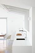 weiße Küchenzeile unter Dachschräge im Designerstil mit weißem Schalenstuhl vor Fenstertür