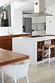 Essplatz mit weißem Schalenstuhl neben Küchenblock und Barhocker in offener weißer Designer Küche