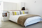 Modern double bed with throw against partition in sleeping area