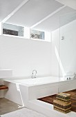 Designer bathroom with bathtub on platform opposite shower area with glass partition