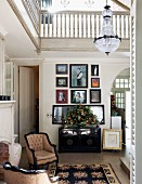 Gallery of pictures above Colonial-style cabinet and antique upholstered armchairs in double-height hall with encircling gallery
