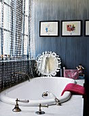 Bathtub with retro tap fittings in marble surround; pictures from Tintin comics on blue-stained wall cladding