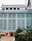 Extension with closed, turquoise shutters on stone foundation; raised flower beds and gravel paths