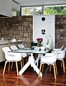 Dining area with Italian shell chairs at glass table; white cupboard against stone wall in background
