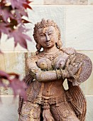 Statue of Oriental goddess; blurred foliage in background