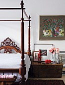 Dark-wood, Colonial-style canopy bed; red ethnic figurine on bedside cabinet and Na