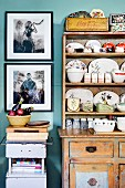 Collection of china crockery in shabby chic kitchen dresser and framed photo art on wall