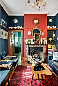 Red and blue living room with retro furniture, collectors' items and open fireplace