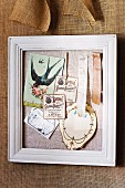 Fabric in white picture frame used as pinboard for romantic vintage decorations