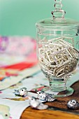 Rhinestone buckles in goblet-shaped, lidded glass jar and small silver bird ornaments