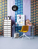 Mixture of boldly patterned wallpapers as backdrop for modern office area with tall, neutral-coloured set of drawers, plexiglass table and swivel chair