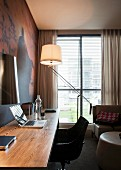Desk, swivel chair and classic, designer lamp against wall with photo wallpaper in living room