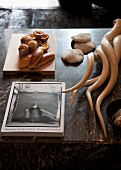 Still-life arrangement of book, pastries and hunting trophies on marble table