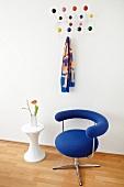 Bauhaus Drehstuhl mit blauem Bezug und Beistelltisch vor Wand mit gehängter Klassiker Garderobe