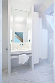 White designer bathroom - screened marble washstand next to white suspended cupboards below sloping ceiling