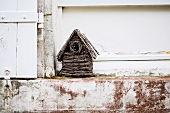 Wicker bird box on weathered stone step outside house