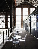Row of tables and ghost chairs in former, repurposed factory hall
