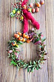 Wreath of spirea twigs and rosehips with felt cord on wedding reception table