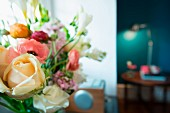 Bouquet of ranunculus, freesias and roses in delicate shades against blurred background