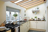 Bright, country-house-style fitted kitchen with glass ceiling
