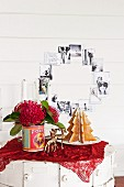 Australian Advent arrangement of gingerbread Christmas tree, deer-shaped candlesticks and pincushion proteas in tin can in front of black and white family photos