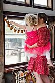 Mutter mit Tochter vor selbstgemachter Adventskalender-Girlande am Fenster