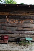 Flexible light strip spelling the word 'Love' on exterior wall of wooden cabin