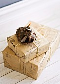 Presents wrapped in pale brown paper cutting patterns and bird ornament with real feathers