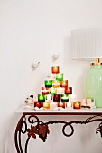 Pyramid of colourful tealight holders next to table lamp on console table