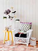 White wicker chair with cushions next to yellow-painted side table against white wooden wall and house plants in planters suspended from ceiling