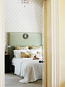 View through open bedroom door of double bed with pastel green, upholstered headboard decorated with silver wreath