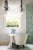Free-standing bathtub below open window with gathered drape