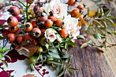 Autumnal wreath of various rosehips, roses and branches of spirea