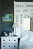 White-painted bedside cabinet and decorative frame of perforated wood above bed